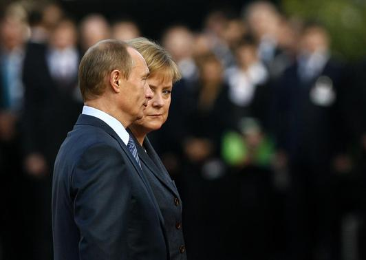 German Chancellor Angela Merkel (R) and Russian President Vladimir Putin listen to their countries national anthems prior to St. Petersburg Dialogue forum in Wiesbaden, in this October 15, 2007 file photo.  REUTERS-Kai Pfaffenbach-Files