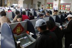 Частные инвесторы в брокерской конторе в Шанхае 17 ноября 2014 года. Азиатские фондовые рынки, кроме Японии, снизились в понедельник на фоне падения цен на нефть до пятилетнего минимума и ухудшения макроэкономической статистики Китая. REUTERS/Aly Song