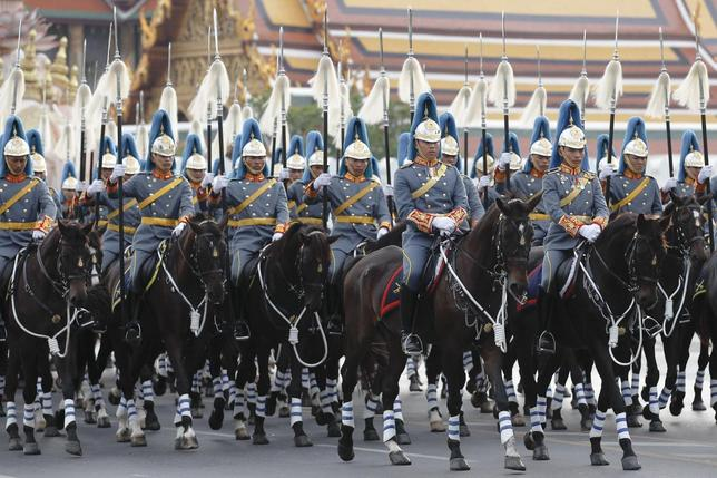 Thai Royal Guards ride their horses in front of the Grand Palace, during a military parade as a part of a celebration for the upcoming birthday of Thailand's King Bhumibol Adulyadej, in Bangkok, December 2, 2014. REUTERS/Chaiwat Subprasom