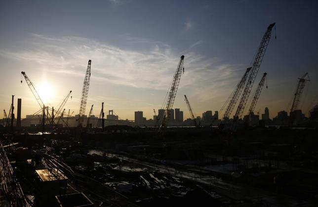 Cranes are pictured at a construction site at the coastal area of Tokyo Bay in Tokyo November 27, 2014. REUTERS/Issei Kato