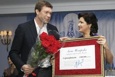 Opera singer Anna Netrebko (R) hands over a symbolic cheque to Oleg Tsaryov, former deputy of the Ukrainian parliament and pro-Russian politician, during a charitable ceremony and news conference in St. Petersburg, December 7, 2014.  REUTERS/Stringer