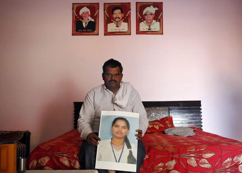 Veer Pal Chauhan, 44, poses with the picture of his daughter Pinki Cahuhan, who died after committing suicide, in Manesar in Haryana in this November 28, 2014 photoREUTERS/Anindito Mukherjee