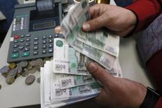 Un trabajador cuenta rublos rusos dentro de una oficina en Krasnoyarsk. Imagen de archivo, 6 noviembre, 2014. El banco central de Rusia subió el jueves su principal tasa de financiamiento en 100 puntos básicos a 10,5 por ciento, en línea con las expectativas de los analistas, ante una aceleración de la inflación y expectativas crecientes de depreciación para el rublo. REUTERS/Ilya Naymushin