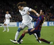David Luiz disputa lance com Busquets em partida do PSG com o Barcelona. 10/12/2014.   REUTERS/Albert Gea