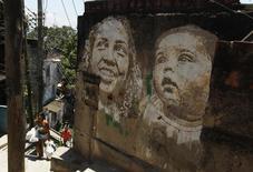 Pessoas passam por obra do artista português Alexandre Farto no Morro da Providência, no Rio de Janeiro. 29/11/2012 REUTERS/Pilar Olivares