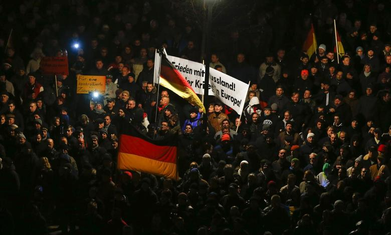 Participants hold German national flags during a demonstration called by anti-immigration group PEGIDA, a German abbreviation for ''Patriotic Europeans against the Islamization of the West'', in Dresden December 8, 2014. REUTERS/Hannibal Hanschke