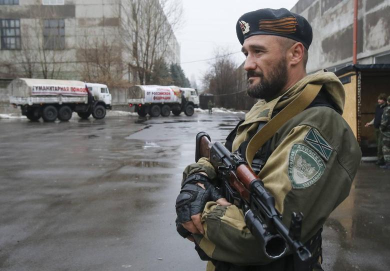 A pro-Russian-separatist patrols the street in front of Russian humanitarian trucks in Makiivka (Makeyevka) in Donetsk region, December 12, 2014. REUTERS/Maxim Shemetov