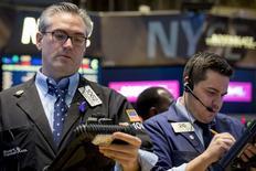 Unos operadores en la bolsa de Wall Street en Nueva York, dic 15 2014. Las acciones caían el lunes en la bolsa de Nueva York luego de que se desvanecieran unas ganancias iniciales originadas por un breve repunte en los precios del crudo. REUTERS/Brendan McDermid