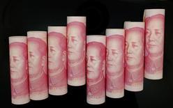 Billetes de 100 yuan en una ilustración fotográfica realizada en Pekín, nov 5 2013. El regulador de seguros de China dijo el lunes que creará un nuevo plan de financiamiento que podría destinar hasta 200.000 millones de yuanes (32.000 millones de dólares) de fondos de empresas de seguros para respaldar a pequeñas empresas y a firmas que inicien actividades. REUTERS/Jason Lee
