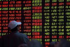 Personas observan una pantalla que muestra índices económicos en Shanghái, 15 diciembre, 2014. La caída de los precios del petróleo y una encuesta pesimista de manufactura en China pesaban sobre las bolsas de Asia el martes, mientras que el rublo subía frente al dólar después de que Rusia elevó su tasa de interés de referencia en un intento por detener el colapso de su moneda. REUTERS/Aly Song