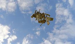 Долларовые купюры в небе над пригородом Севильи 16 ноября 2014 года. Министерство финансов РФ начало продавать валютные остатки федерального бюджета, которые на данный момент составляют $7 миллиардов, объем продаж будет зависеть от ситуации, сказал Рейтер глава департамента Минфина Максим Орешкин. REUTERS/Marcelo Del Pozo