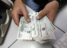 Un empleado cuenta rublos en una oficina privada en Krasnoyarsk, Rusua, dic 17 2014. La economía rusa se estancó en noviembre, mostraron datos publicados el miércoles, lo que hace más probable que el colapso del rublo en este mes la empuje a la recesión el próximo año. REUTERS/Ilya Naymushin