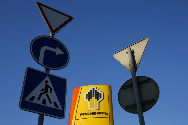 Traffic signs are seen in front of a gasoline station of Russia's top crude producer Rosneft in Moscow, in this October 29, 2014 file photo. REUTERS/Maxim Shemetov/Files