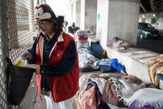 Blanca Rodriguez, 46, cleans up her sleeping area under an overpass in Chicago, December 4, 2014. Rodriguez has been living under the overpass for 3 months. REUTERS/Andrew Nelles