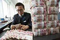 Un empleado cuenta billetes de yuan en un banco en Nantong. Imagen de archivo, 2 diciembre, 2014. China relajará sus restricciones sobre las operaciones en yuanes de los bancos a partir de 2015, en un pequeño, pero significativo paso hacia la flexibilización de los controles de capital. REUTERS/China Daily