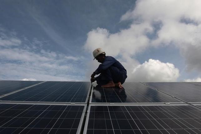 A worker adjusts solar panels at a park on the outskirts of Havana September 24, 2013. REUTERS/Stringer/Files