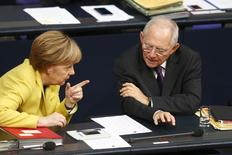 German chancellor Angela Merkel talks with Finance Minister Wolfgang Schaeuble prior to a vote on the federal budget, at the lower house of parliament Bundestag in Berlin November 28, 2014.     REUTERS/Hannibal Hanschke