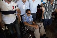 Former boxer Muhammad Ali of the U.S. sits in a wheelchair as he is taken to a photo session with attendees of the 50th Convention of the World Boxing Council in Cancun December 4, 2012. REUTERS/Victor Ruiz Garcia