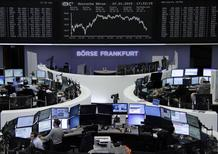 Traders are pictured at their desks in front of the German share price index DAX board at the Frankfurt stock exchange January 7, 2015. REUTERS/Remote/Stringer
