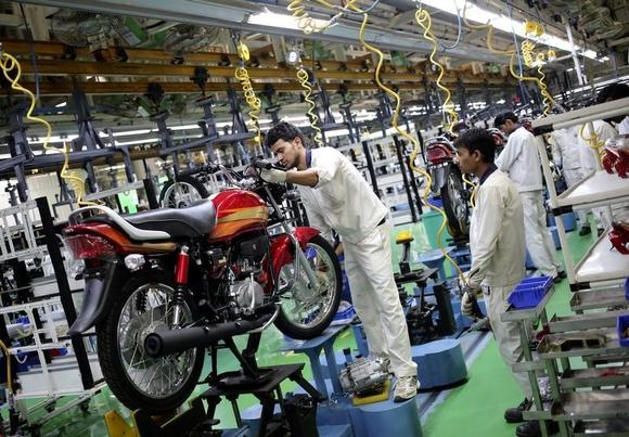 Employees work on an assembly line of Hero Motocorp during a media tour to the newly opened plant in Neemrana, in the desert Indian state of Rajasthan, October 20, 2014. REUTERS/Anindito Mukherjee