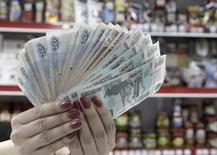 """Кассир показывает рублевые купюры в магазине в Ставрополе 7 января 2015 года. Рубль в минусе на первой полноценной биржевой сессии января, дешевея вслед за нефтяными котировками и перед угрозой снижения кредитного рейтинга РФ до """"мусорного"""" статуса уже на текущей неделе. REUTERS/Eduard Korniyenko"""