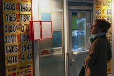 Женщина у пункта обмена валюты в Киеве. 7 ноября 2014 года. Международные резервы Национального банка Украины упали в декабре 2014 года до самого низкого за десять лет уровня $7,533 миллиарда, сократившись за год на 63 процента или почти на $12,9 миллиарда, что стало самым сильным годовым падением за всю историю страны, сообщил предварительные данные центральный банк. REUTERS/Valentyn Ogirenko