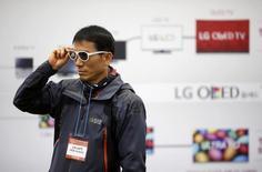 Человек примеряет пару 3D-очков на стенде LG Electronics на выставке Korea Electronics Show в Кояне 17 октября 2014 года. Министерство труда Южной Кореи распорядилось прекратить производство на заводе LG Display Co Ltd, производящем ТВ-панели на органических светодиодах (OLED), из-за утечки газообразного азота. REUTERS/Kim Hong-Ji