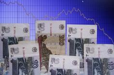 Рублевые купюры на фоне графика колебаний курса пары доллар/рубль в Варшаве 5 ноября 2014 года. Рубль дешевеет утром среды вслед за нефтью, а также валютами сырьевых и развивающихся рынков на фоне снижения Всемирным банком прогнозов глобального экономического роста и пересмотра им в худшую сторону прогнозов падения российской экономики. REUTERS/Kacper Pempel