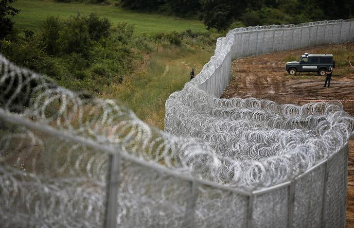 Bulgarian border police stand near a barbed wire fence on the Bulgarian-Turkish border July 17, 2014. REUTERS/Stoyan Nenov