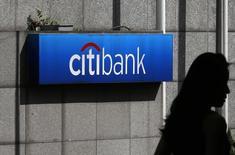 Женщина проходит мимо логотипа Citibank в Гонконге 28 июля 2014 года. Citigroup, отказавшаяся от розничных банковских операций на нескольких международных рынках, получила очень скромную прибыль в четвертом квартале 2014 года после уплаты $3,5 миллиарда за судебные тяжбы и реструктуризацию бизнеса. REUTERS/Bobby Yip