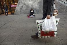 Una persona camina con bolsas de compras frente un hombre que pide limosnas en Sevilla. Imagen de archivo, 7 enero, 2015. Más de la mitad de la riqueza mundial estará en manos de sólo un uno por ciento de la población el próximo año al aumentar con fuerza la desigualdad global, dijo el lunes la organización caritativa contra la pobreza Oxfam. REUTERS/Marcelo del Pozo