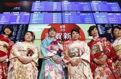 """Женщины в кимоно позируют фотографам на фондовой бирже в Токио во время церемонии по случаю открытия торгов после новогодних праздников. 5 января 2014 года. Азиатские фондовые рынки выросли во вторник за счет отчета о ВВП Китая и ожиданий """"количественного смягчения"""" Европейского центробанка. REUTERS/Yuya Shino"""