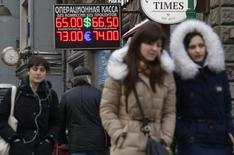 People walk past a board showing currency exchange rates in Moscow, January 26, 2015. REUTERS/Maxim Zmeyev