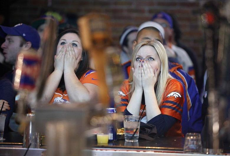 Denver Broncos fans react to a turnover as they watch their team's NFL Super Bowl XLVIII against the Seattle Seahawks at LoDo's Bar and Grill in Denver, Colorado in this February 2, 2014 file photo.  REUTERS/Marc Piscotty/Files