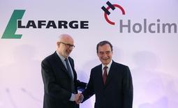 Le président de Holcim, Rolf Soiron (à gauche), et le PDG de Lafarge, Bruno Lafont. Les cimentiers suisse et français ont confirmé la cession d'un ensemble d'actifs au groupe irlandais de matériaux de construction CRH pour une valeur d'entreprise de 6,5 milliards d'euros dans le cadre de leur projet de fusion. /Photo prise le 7 avril 2014/REUTERS/Christian Hartmann