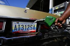 A worker fills up a car with fuel at a gas station in Caracas, January 12, 2015.   REUTERS/Jorge Silva