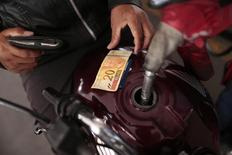 A gas station employee refuels a motorcycle in Brasilia November 7, 2014. REUTERS/Ueslei Marcelino