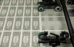Billetes de un dólar en la Casa de la Moneda de Estados Unidos en Washington, nov 14 2014. La probabilidad de que el euro caiga este año para cotizar en paridad con el dólar, o en niveles más bajos, es de un 30 por ciento, según un sondeo de Reuters a estrategas cambiarios, a pesar de las crecientes dudas sobre el momento en que subirán las tasas de interés en Estados Unidos.   REUTERS/Gary Cameron