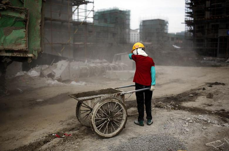 Ou Mei, a 45-year-old female migrant construction worker, shields her face from dust during a shift at a residential construction site in Shanghai in this July 2, 2013 file photo.  REUTERS/Aly Song/Files
