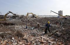 Trabalhadores coletam barras de aço de sucata numa demolição em Hangzhou, China. 29/07/2014 REUTERS/William Hong