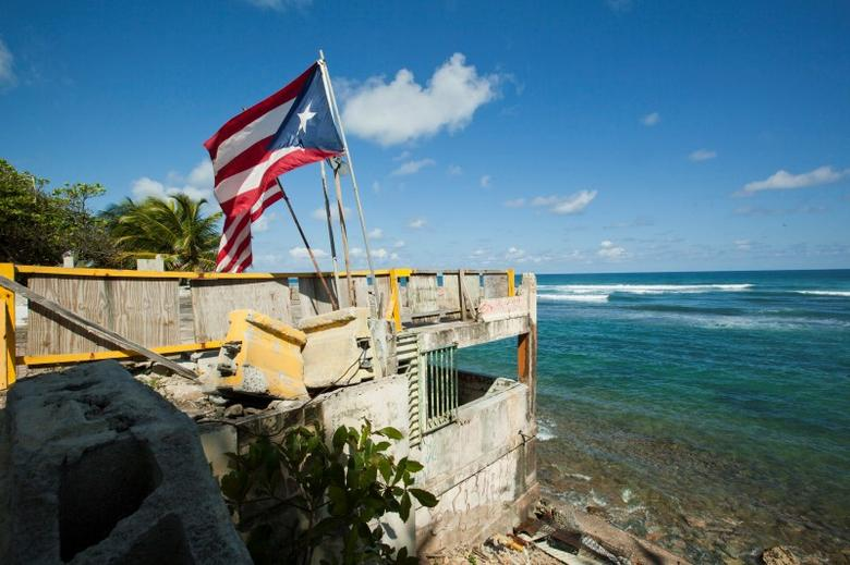 Puerto Rico and U.S. flags flutter on a building that once belonged to a restaurant, in San Juan March 11, 2014. REUTERS/Ana Martinez