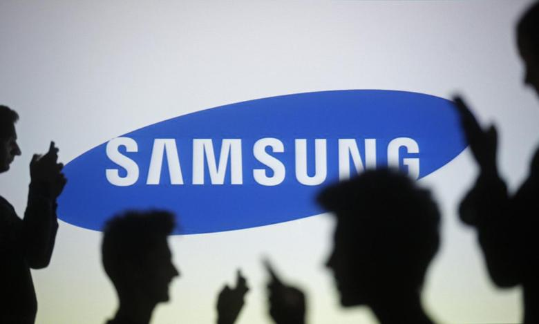 People are silhouetted as they pose with mobile devices in front of a screen projected with a Samsung logo, in this file picture illustration taken in Zenica October 29, 2014. REUTERS/Dado Ruvic/Files