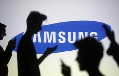 Fotografia ilustrativa de pessoas em frente uma tela com o logo da Samsung projetado. 29/10/2014    REUTERS/Dado Ruvic