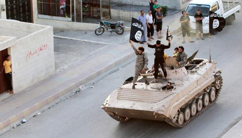 Militant Islamist fighters hold the flag of Islamic State while taking part in a military parade along the streets of northern Raqqa province, June 30, 2014.   REUTERS/Stringer