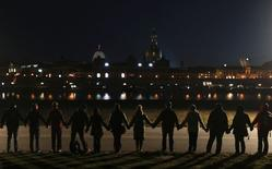 People hold hands as they form a human chain on the embankment of Elbe river in Dresden, February 13, 2015.  REUTERS/David W Cerny