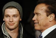 "Actor and former California governor Arnold Schwarzenegger (R) poses with his son Patrick as they arrive for the British premiere of ""The Last Stand"", at Leicester Square in London January 22, 2013.  REUTERS/Luke MacGregor"