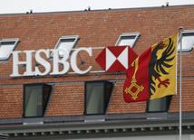 A HSBC logo is pictured behind the flag of the canton of Geneva at a Swiss branch of the bank in Geneva February 18, 2015. REUTERS/Denis Balibouse