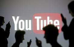 Pessoas em frente ao logo do Youtube em foto ilustrativa. 29/10/2014  REUTERS/Dado Ruvic