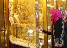 Женщина у витрины ювелирного магазина в Басре. 14 февраля 2015 года. Цены на золото растут благодаря ослаблению доллара после публикации протокола совещания ФРС, показавшего, что руководство центробанка опасается слишком раннего повышения процентных ставок. REUTERS/ Essam Al-Sudani