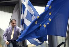 A man adjusts a Greek (L) and a European flag outside the Greek embassy in Brussels February 19, 2015. REUTERS/Yves Herman